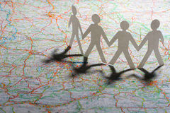 Group Travel. Team or family concept: Paper people holding hands. backlit with long shadows on the map Stock Image