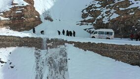 A group of travelers clearing roadblock by removing snow from dangerous roads of spiti