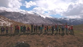 The group of travelers in the mountains raise their hands stock video footage