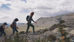 Group of travelers up the mountain. family travelers in the mountains. mother and two children went Hiking in the. Mountains stock video