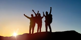 Group of travellers with backpacks over sunrise royalty free stock photos