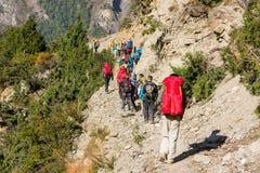 Group of trekkers on Annapurna circuit in Nepal. Hikers walking in line Stock Image