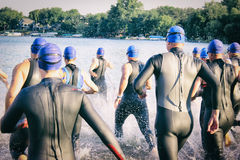 Group of Triathletes with Blue Swim Caps Runs into Lake for Race Stock Photo