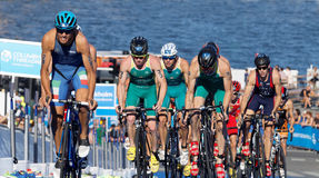 Group of triathlon competitors cycling uphill Stock Image