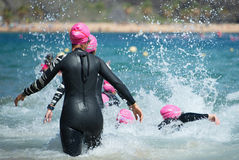 Group triathlon participants running into the water for swim portion of race. Splash of water and athletes running stock image