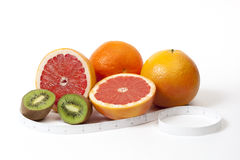 Group of tropical fruits and tape measure in inches over white Stock Image