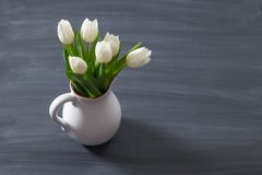 Bouquet of tulips in a oldfashioned rustic vase pot. Light colour flowers in white jug on a blur background. A group of tulip flowers gathered on a medium dark Stock Image