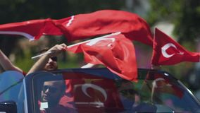 Group of turkish residents waving flags of their country while sitting in car. Stock footage stock footage