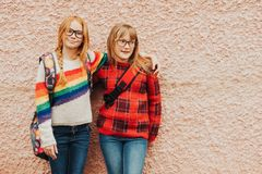 Group of two adorable kid girls with school backpacks wearing glasses. Group of two adorable kid girls posing outdoors against pink wall, wearing glasses, school stock images