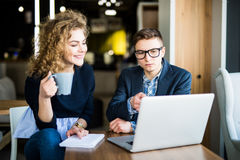 Group of two coworkers working over laptop discuss in a modern office. Woman drink coffee. Group of two coworkers working over laptop discuss in a modern office Stock Photo