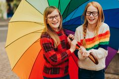 Group of two cute little girls playing outside under big colorful umbrella stock photos
