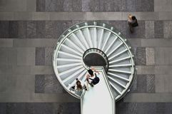 Circular stair overview. Group of two descends a circular staricase to the next level overview. pedestrian activity buildng interiors staris Rundtreppe Ü royalty free stock photos