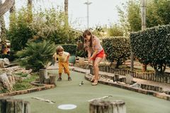 Group of two funny kids playing mini golf. Children enjoying summer vacation Stock Image