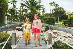 Group of two funny kids playing mini golf. Children enjoying summer vacation Stock Photo