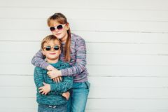 Group of two funny kids playing together outside. Little boy and girl posing against white wooden background, brother and sister wearing matching pullovers Royalty Free Stock Image