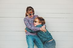 Group of two funny kids playing together outside. Little boy and girl posing against white wooden background, brother and sister wearing matching pullovers Stock Photography