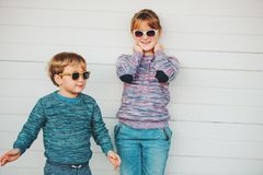 Group of two funny kids playing together outside. Little boy and girl posing against white wooden background, brother and sister wearing matching pullovers royalty free stock images