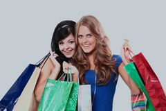 Group of two happy young adult women out of shopping with colored bags. Group of two happy young adult women out of shopping with colored bags Royalty Free Stock Images