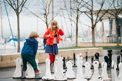 Group of two kids playing giant chess on playground. Wearing rain coats and boots. Image taken in Ouchy, Lausanne, Switzerland Royalty Free Stock Photos
