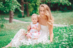 Group of two people, white Caucasian mother and baby girl child in white dress sitting playing in green summer park forest outside Stock Images