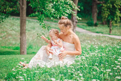 Group of two people, white Caucasian mother and baby girl child in white dress sitting playing in green summer park forest outside Royalty Free Stock Photo