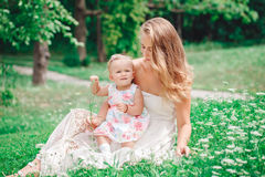 Group of two people, white Caucasian mother and baby girl child in white dress sitting playing in green summer park forest outside Royalty Free Stock Images