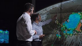 Researchers forecasting weather of storm. Group of two scientists observing and tracking hurricane on map and analyzing weather. Elements of this image furnished stock images