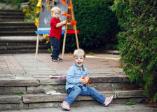 Group of two white Caucasian toddler children kids boy and girl outside in summer autumn park by drawing easel Royalty Free Stock Photos