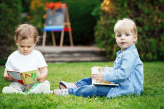 Group of two white Caucasian toddler children kids boy and girl sitting outside in grass in summer autumn park Stock Photo