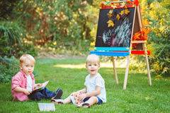 Group of two white Caucasian toddler children kids boy and girl sitting outside in summer autumn park by drawing easel Stock Photo