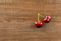 Fresh raw red sweet cherry on brown wood. Group of two whole sweet bright red cherry flatlay on brown wood royalty free stock image