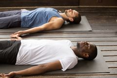 Group of sporty people in Dead Body pose. Group of two young afro american and caucasian sporty people practicing yoga lesson lying in Dead Body or Corpse pose stock photos