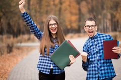 Group of two young euphoric students happy passed exam with hands up walk in park royalty free stock photography