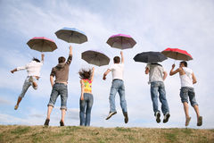 Group with umbrellas Stock Images