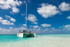 Group of unidentified tourists travel on a catamaran near the island of Kayo Largo. White catamaran on a background of blue sky stock image