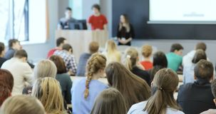Group of university students sitting at their desks in auditorium and listening as their teacher holds a lecture. View from behind of a group of students in a stock footage