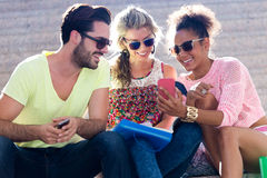 Group of university students using mobile phone in the street. Royalty Free Stock Image