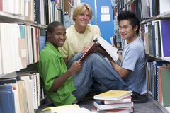Group of university students working in library. Group of three male students sitting on floor of library surrounded by books royalty free stock images