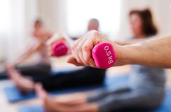 Group of senior people doing exercise with dumbbells in community center club. stock photos