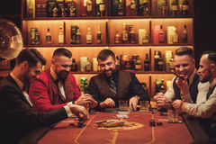 Group of upper class men playing poker in gentlemen`s club Stock Photography