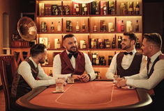 Group of upper class men playing poker in gentlemen`s club Royalty Free Stock Photo
