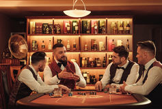 Group of upper class men playing poker in gentlemen`s club. Group of men playing poker in gentlemen`s club Stock Images