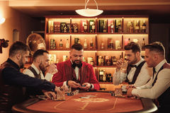 Group of upper class men playing poker in gentlemen`s club. Group of men playing poker in gentlemen`s club Stock Photo