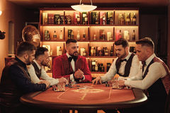 Group of upper class men playing poker in gentlemen`s club Royalty Free Stock Image