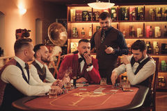 Group of upper class men playing poker in gentlemen`s club. Group of men playing poker in gentlemen`s club Stock Photos