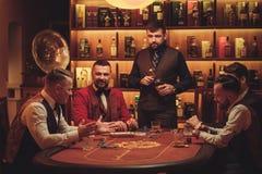 Group of upper class men playing poker in gentlemen`s club Stock Image