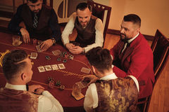 Group of upper class men playing poker in gentlemen`s club Royalty Free Stock Images