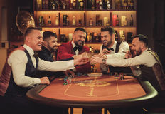 Group of upper class men toasting in gentlemen`s club. Group of men playing poker in gentlemen`s club Royalty Free Stock Images