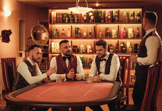 Group of upper class men toasting in gentlemen`s club. Group of men playing poker in gentlemen`s club Stock Photos