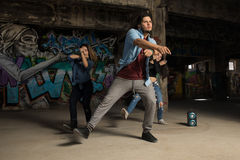 Group of urban dancers performing. Three young dancers freestyling with some music in an abandoned building Stock Image